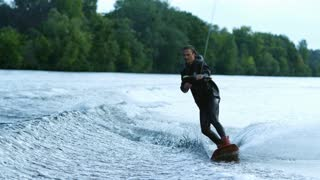 Athlete doing tricks on wakeboard. Young man wakeboarding on river wave. Wake boarding on city lake in slow motion. Male rider waterskiing. Extreme sports on city lake. Extreme lifestyle