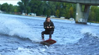 Athlete wakeboarder jumping high above water. Extreme stunt over water. Professional trick in training for waterskiing. Sportsman dissatisfied with his action. Extreme water sports training