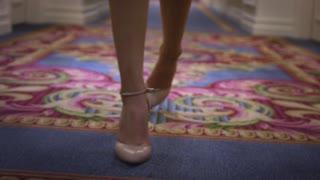 Attractive woman in beige shoes walking on carpet floor in long corridor. Close up female legs in high heeled shoes walking on corridor front view
