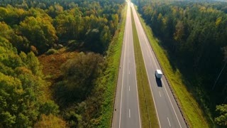 Automobile traffic at highway road at forest. Highway road in forest landscape. Cars on highway at nature. Asphalt road at autumn forest. Aerial landscape of highway road