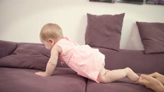 Baby crawling away mother. Cheerful kid walking on sofa. Beautiful child girl crawl on bed with mom. Adorable childhood. Home life concept. Mother playing with baby