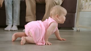 Baby crawling on floor at home. Happy family concept. Cute baby girl crawl in home with parents. Adorable child walking on floor. Toddler walking in home. Sweet childhood