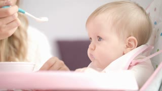 Baby eating puree with spoon. Close up of infant baby face eat baby food. Mom feed kid. Mother feeding child with porridge. Little girl eating puree
