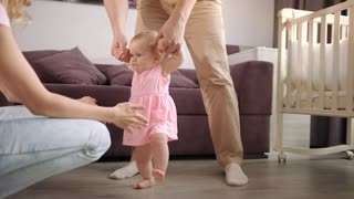 Baby first steps. Parents learning walk kid. Father holding child hands. Baby walking at home. Family support little kid. Baby learning to walk