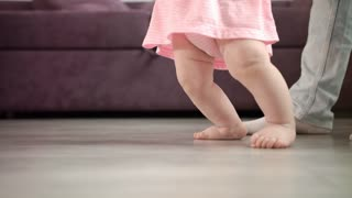 Baby girl doing first steps at home. Child feet walking on floor with father support. Baby learn to walk with daddy. Infant learning walk. Little feet step at home