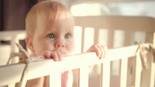 Baby standing in bed at home. Portrait of baby girl stand in cot. Baby eyes looking for mother. Sad toddler waiting for parents. Little child in bed. Sweet infant at home