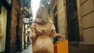 Back view of sexy woman walking with shopping bags. Close up smiling girl flirting on camera in slow motion. Beautiful woman going away in old city street.