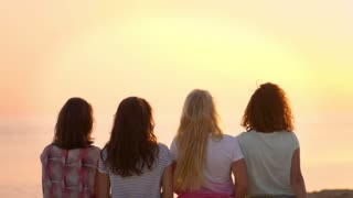 Back view of sitting woman enjoy beach sunset. Four young girls watching sunset in slow motion. Women on tropical vacation enjoying sunset at sea. Enjoy summertime. Female lifestyle on Cyprus vacation