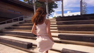 Back view of woman in dress running stairs. Elegant woman run stairs in slow motion. Running woman in sunny day. Sunglasses girl run stairs in Cyprus city