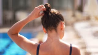 Back view of woman shaking wet hair. Close up of female hair on summer vacation. Brunette girl shaking head on summer resort. Enjoy summertime. Female brunette shaking hair