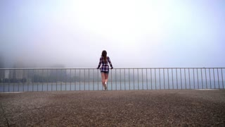 Back view of woman waving hand. Young woman raise hand for make someone to see her. Back view of woman standing at sea city. Lifestyle concept. Woman enjoying life. Girl looking on city fog