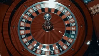 Ball quickly spinning around in casino roulette. Close up wooden roulette wheel. Traditional game of chance. Classic gambling game in luxury casino. Rotating gambling machine