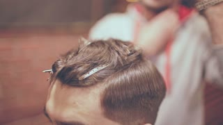 Barber haircut. Man hairdresser removing hair pins from man head. Hair barrette on male head in barbershop. Male hairstyle. Hair fashion model. Hairstyling tools