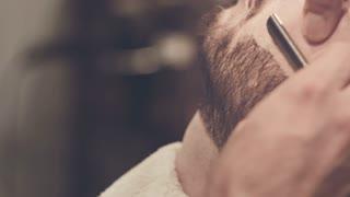Barber shave. Close up of shaving beard in barbershop. Barber shaving. Straight razor shave. Barber shaving beard. Grooming beard. Barbershop. Man hairdresser doing haircut beard