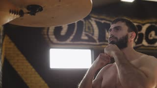 Bearded boxer training with speed bag. Young boxer practicing punches before competition in gym. Boxer exercising kicks on speed bag in slow motion. Boxer training in gym