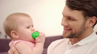 Bearded daddy kissing baby infant. Close up of father holding child with toy. Father kissing baby. Parent care kid. Family tenderness. Sweet parenting. Happy man with baby