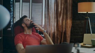 Bearded man relaxing on chair after work at evening in home office. Successful businessman relaxing in cozy office. Success business owner resting at home workplace