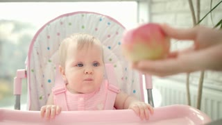 Beautiful baby eating apple in baby chair. Close up of toddler girl gnawing sweet apple. Portrait of cute child tasting fruit. Mother hand give fruit for kid. Healthy nutrition