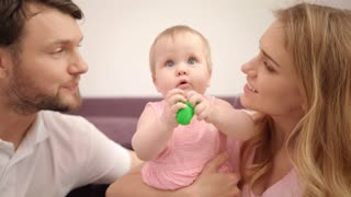 Beautiful family with baby. Happy parents kiss daughter with toy. Sweet family love. Portrait of cheerful mother and father with baby. Mom and dad kissing child girl