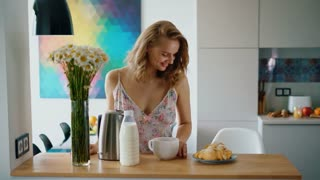 Beautiful girl drinking coffee at kitchen table. Elegant woman have breakfast at home. Morning breakfast with tea and croissants in modern kitchen interior. Morning coffee woman