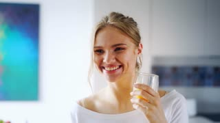 Beautiful girl drinking fresh orange juice from glass. Close up happy woman drinking fruit beverage. Pretty girl in white t-shirt with charming smile standing in kitchen. Healthy and natural nutrition
