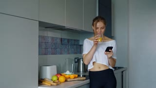 Beautiful girl drinking fresh orange juice from glass. Healthy woman using smartphone while drinking juice. Fit girl in t-shirt and fitness leggings standing in kitchen. Healthy breakfast in morning
