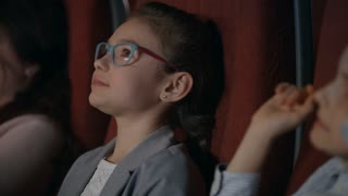 Beautiful girl in glasses watching cartoon film at movie theater. Girl smiling in movie theatre. Cinema kids concept. School girl spending time in cinema. Kid watching movie in slow motion