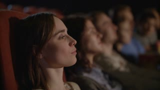 Beautiful girl looking theatre performance. Woman applauding in theatre. Audience applauding artists on stage. Spectators applauding while watching performance in theater