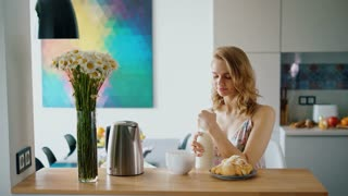 Beautiful girl preparing coffee with milk at kitchen table. Pretty woman pouring milk into coffee mug. Elegant woman having breakfast at home. English breakfast with tea and croissants