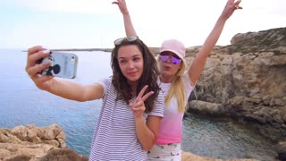 Beautiful girls taking selfie photo on mobile phone at cyprus beach. Two modern girls posing for selfie picture. Happy woman selfie portrait with v sign hand. Woman photo on mobile