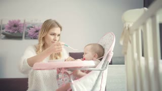 Beautiful mom try feeding baby with porridge. Blondy woman feed kid in baby chair at home. Family care. Infant gnawing teethers