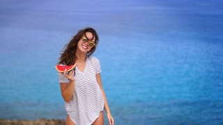 Beautiful woman eating watermelon on sea beach. Woman enjoy summer vacation. Summer girl eating watermelon on sea shore. Happy summertime concept