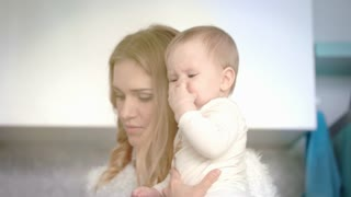 Beautiful woman holding little baby on hand. Mother smiling for infant in white room. Mom happy with child. Close up of blondy woman face smile to little kid. Mother care child