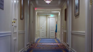 Beautiful woman in blue dress walking along corridor at luxury mansion. Young woman walking to room number in hotel corridor