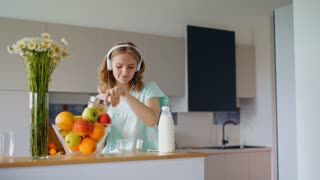 Beautiful woman listening music and cooking. Pretty girl dancing and preparing breakfast. Happy girl in headphones in kitchen. Having fun in morning at home. Woman pouring corn flakes into bowl