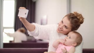Beautiful woman making selfie with baby. Mom making selfie photo with toddler girl. Sweet motherhood. Mother taking mobile photo with child. Mother love. Woman photo with kid