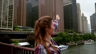 Beautiful woman showing modern city buildings. Brunette woman showing great view of Chicago city. Smiling girl showing by hand Chicago river. Smiling girl showing city skylines. Travel concept