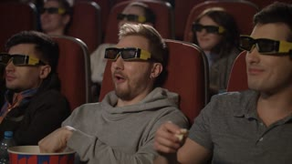 Best friends eating popcorn in movie theater. Friends watching movie in 3d glasses in cinema. Smiling man watching comedy film in cinema. People watching funny film