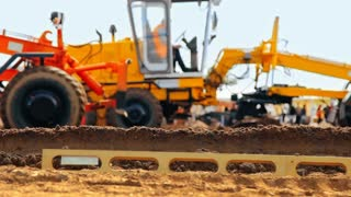 Big motor graders leveling ground on construction site. Heavy machinery in building business. Earthmoving equipment working at quarry. Preparing building territory. Mining industry modern machine
