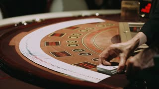 Blackjack dealer during cards shuffle on gambling table. Close up professional croupier hands showing playing cards. Poker table brown surface with classic betting grid. Gambling game in casino