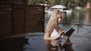 Blonde girl using tablet in jacuzzi outdoor. Sexy woman in white swimsuit touching tablet in hot bath outside. Blonde woman using tablet in wate at luxury resort