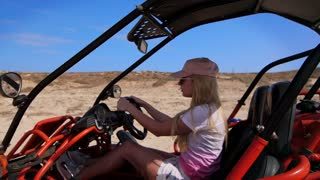 Blonde woman riding buggy car. Female tourist driving on sand buggy. Concentrated woman driver ride in desert buggy. Safari transport. Summer entertainment. Woman drive on sand vehicle