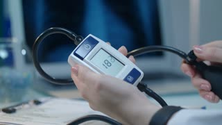 Blood pressure monitor with heart disease. Hypertension concept. Close up of female hand check blood pressure test. Medicine equipment for measure heart pressure
