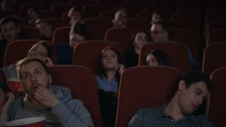 Bored people watching film in cinema. Bored audience leaving cinema while session in slow motion. Guy sleep during movie show. Uninteresting film concept