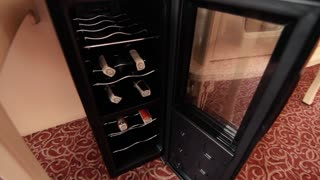 Bottles of wine lying on open mini bar in hotel room. Mini bar with soft drinks bottles on apartments room