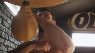 Boxer beat speed bag in gym. Close up of boxer punching bag in slow motion. Handsome boxer training with speed bag in gym. Boxer working hard in sport gym. Man boxing bag