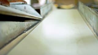 Bread production line. Food factory conveyor belt. Bread loaf on manufacturing line at food plant. Black bread production process. Food conveyor line. Loaf of bread on conveyor belt. Food plant