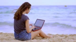 Brunette girl with laptop sitting on sand near sea. Pretty woman using laptop on seashore near waves. Girl using notebook at beach. Female tourist browsing internet online on seashore. Freelance work