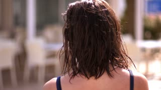 Brunette woman shaking wet hair back view. Close up of walking girl with wet hair. Summer life. Walking woman back after bathing. Enjoy sunbathing. Summer relax