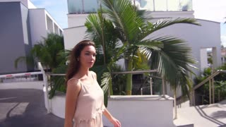 Brunette woman walking in modern city. Close up of brunette model going in sunny day in slow motion. Sunny woman going in tropical city. Walking model in Cyprus city